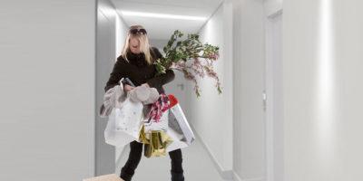 žena před bytovými dveřmi hledá klíče